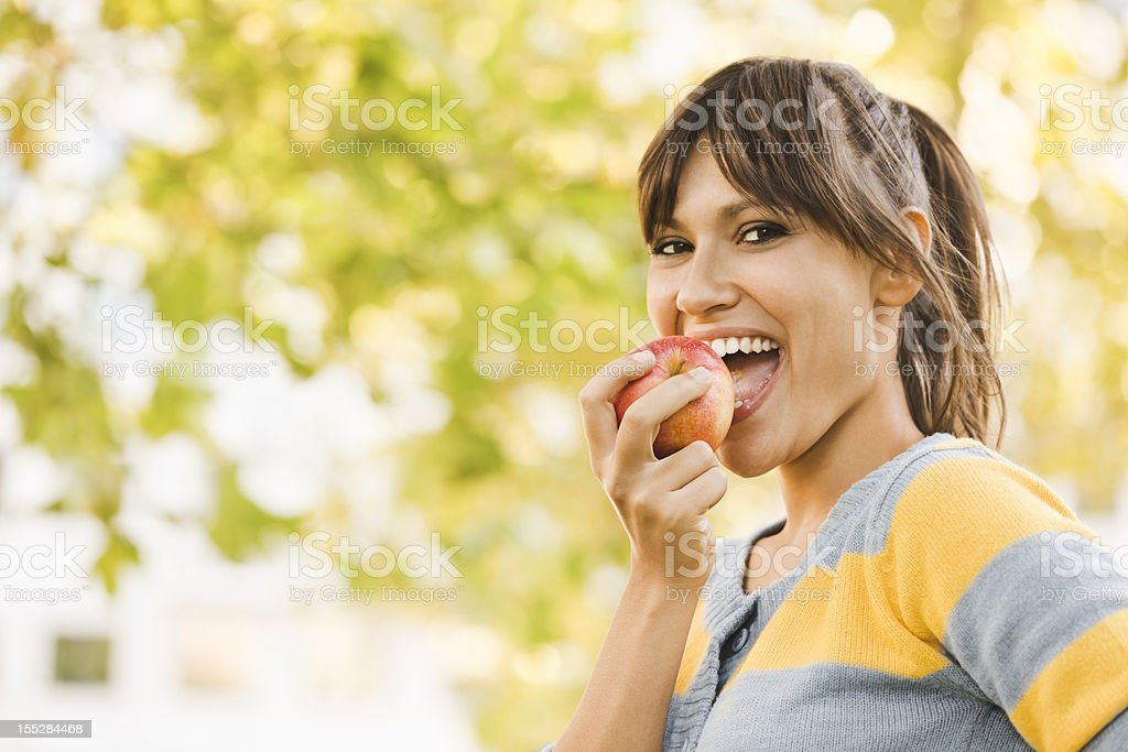 Cheerful young woman eating an apple royalty-free stock photo
