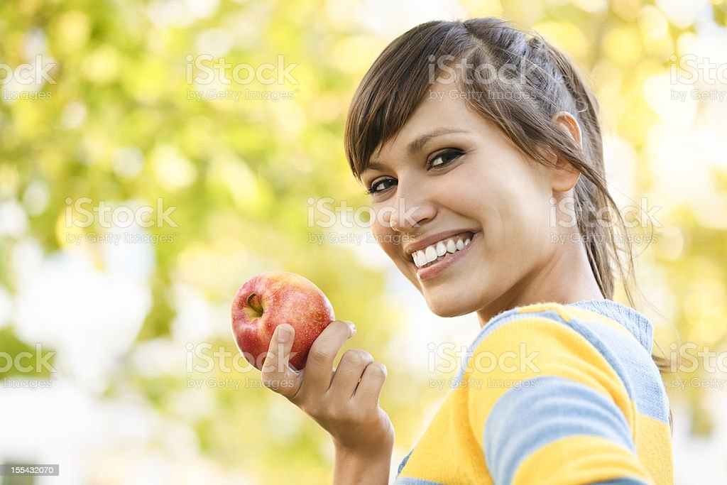 Cheerful young woman eating an apple stock photo