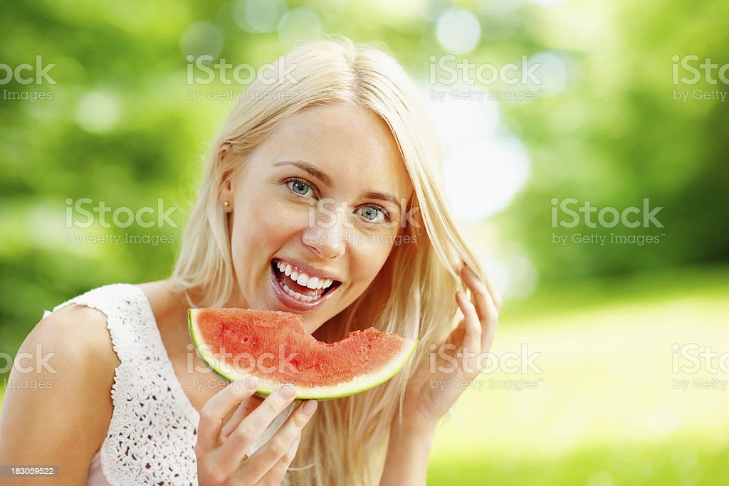 Cheerful young woman eating fresh watermelon royalty-free stock photo