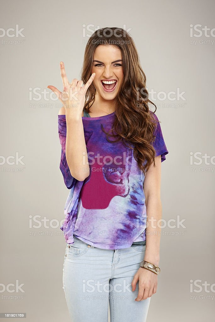 Cheerful young woman gesturing rock on sign royalty-free stock photo
