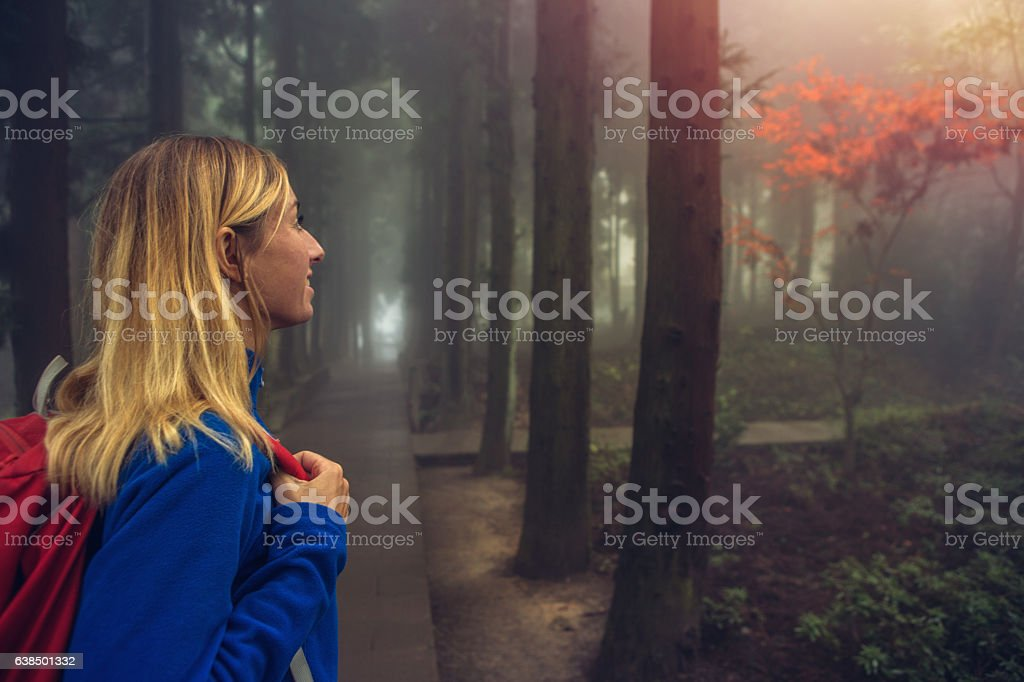 Cheerful young woman hiking in foggy forest, China stock photo