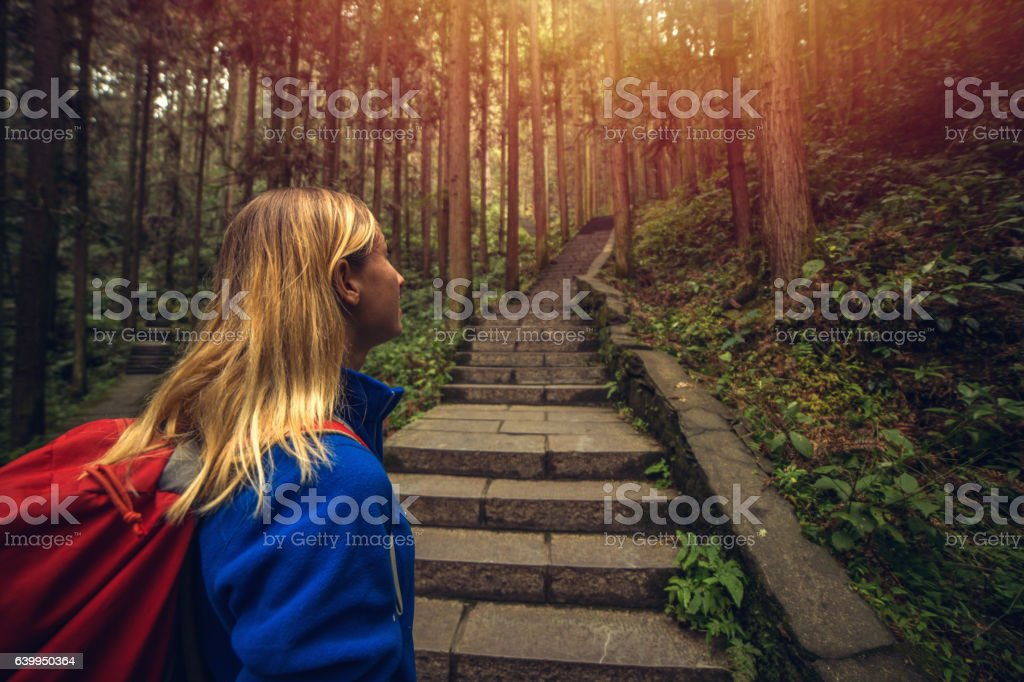 Cheerful young woman hiking in forest, China stock photo