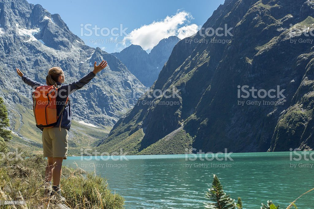 Cheerful young woman hiking reaches the lake Marian, arms outstretched stock photo