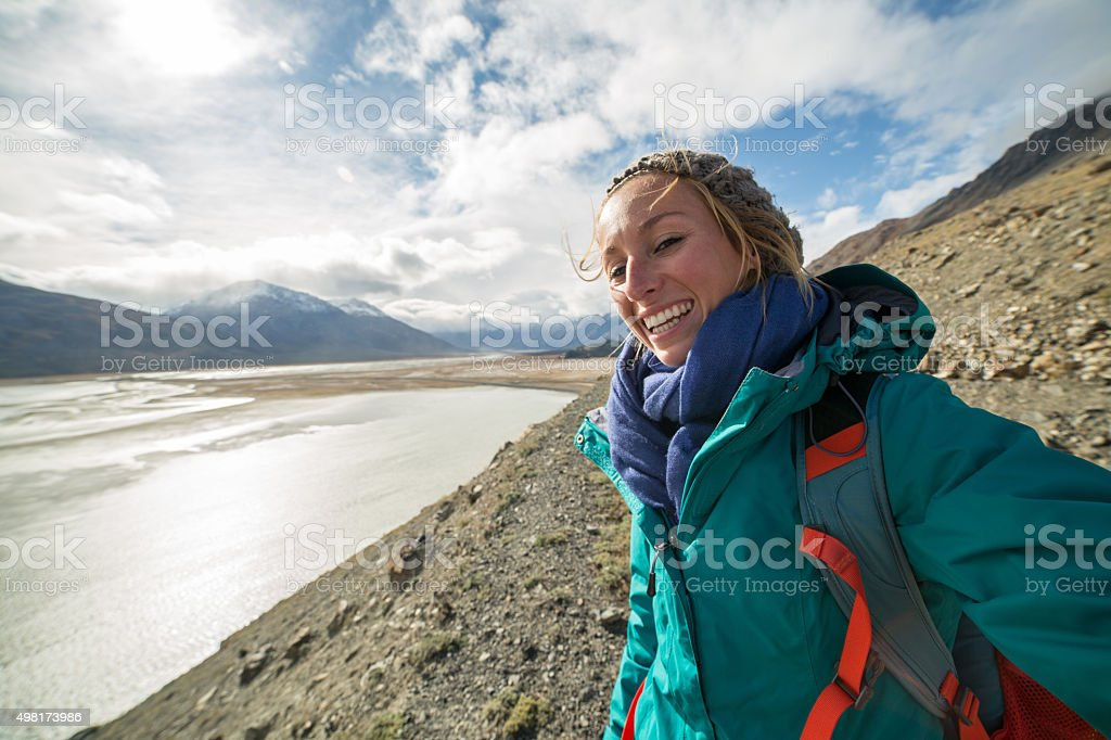 Cheerful young woman hiking takes selfie portrait. Mountain lake stock photo