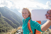 Cheerful young woman hiking taking selfie at mountain top