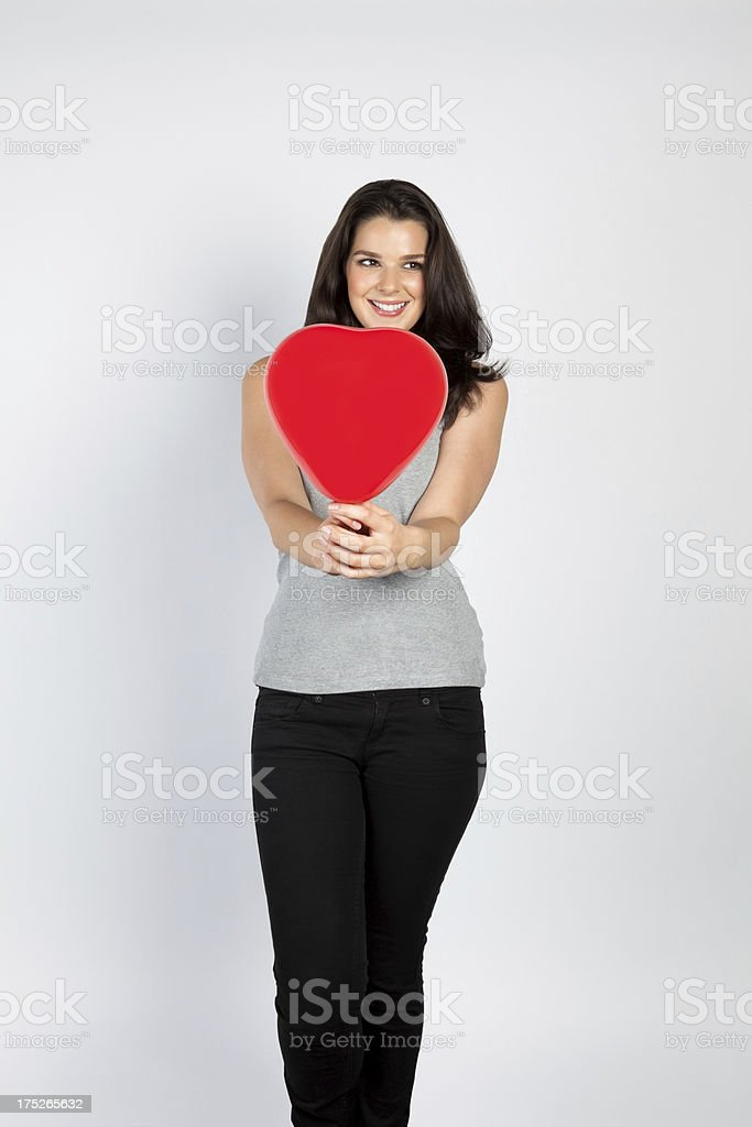 Cheerful young woman holding a heart shaped balloon royalty-free stock photo