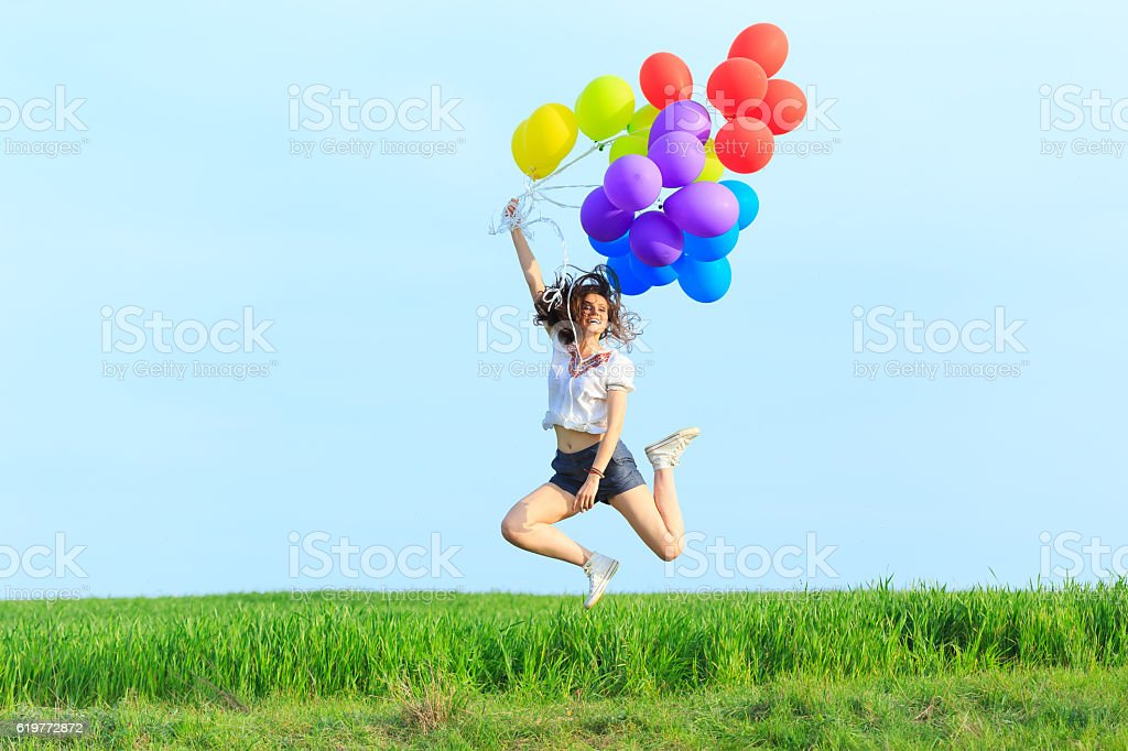 Cheerful young woman holding multicolored balloons jumping stock photo