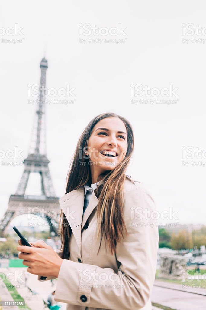 Cheerful young woman holding smart phone stock photo