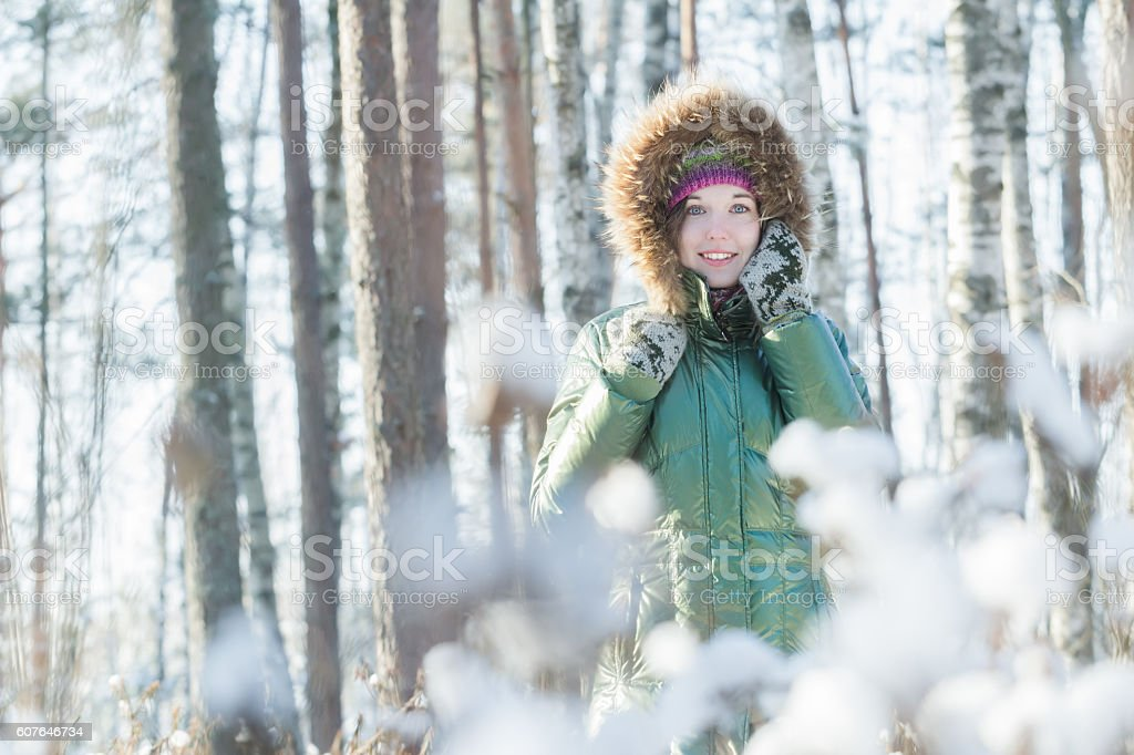 Cheerful young woman holding woolly mittens near her head outdoors stock photo