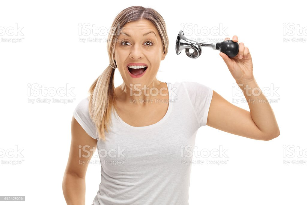 Cheerful young woman honking a horn stock photo