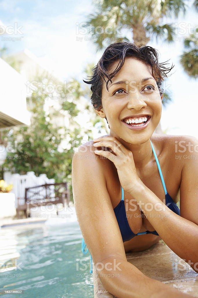 Cheerful young woman in bikini lying by swimming pool royalty-free stock photo