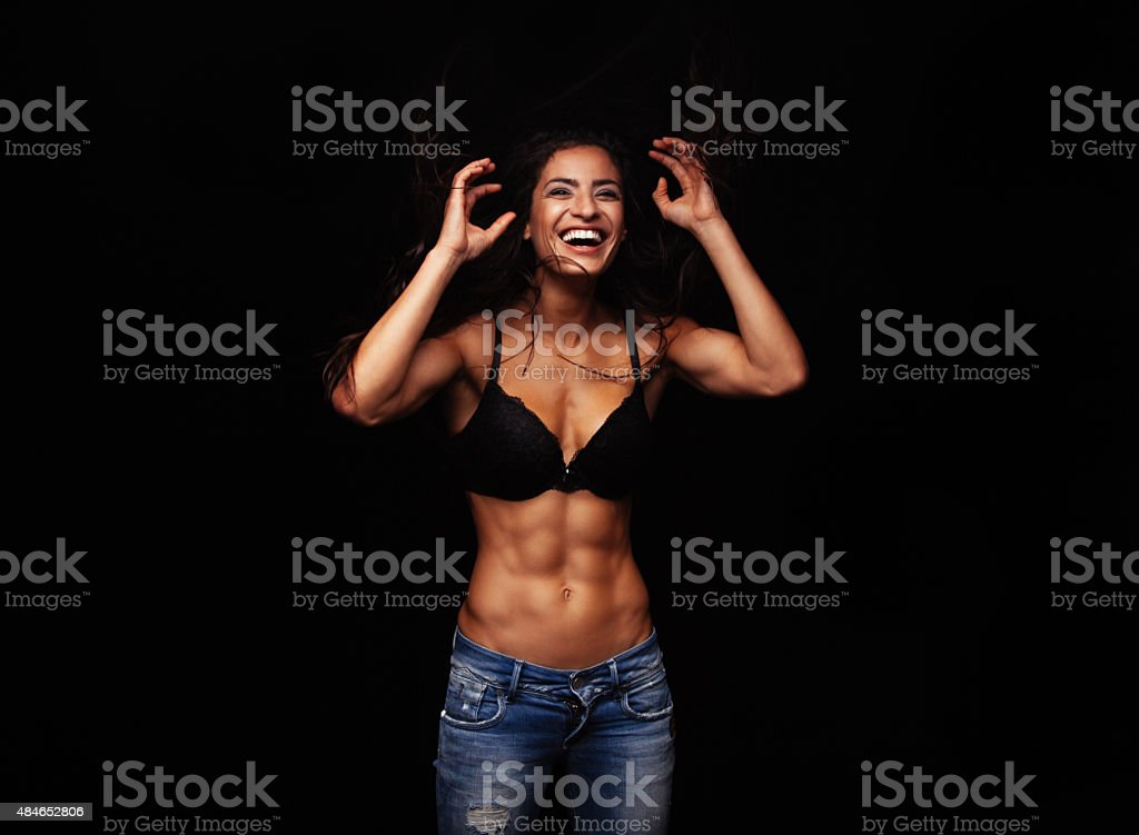 Cheerful young woman in bra and jeans stock photo