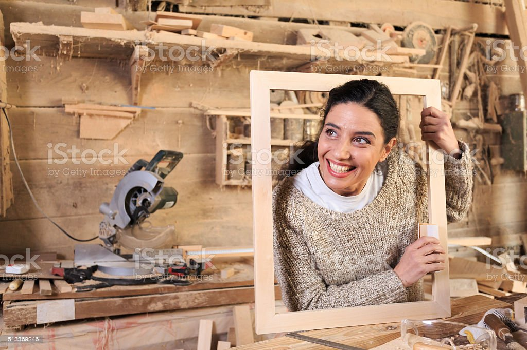 Cheerful young woman in carpenter workshop stock photo
