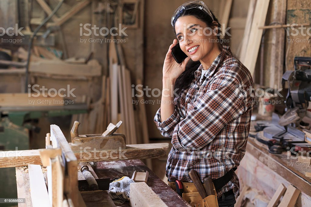 Cheerful young woman in carpenter workshop using phone stock photo
