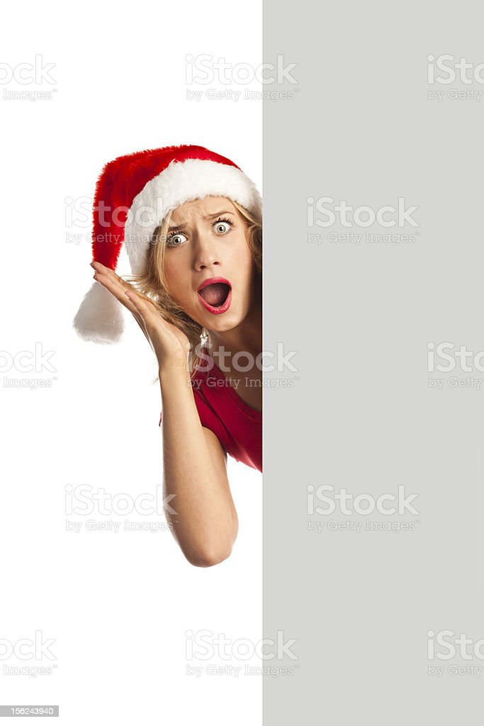 Cheerful young woman in Christmas hat holding blank billboard royalty-free stock photo