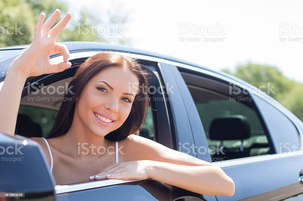 Cheerful young woman is expressing positive emotions in transport stock photo