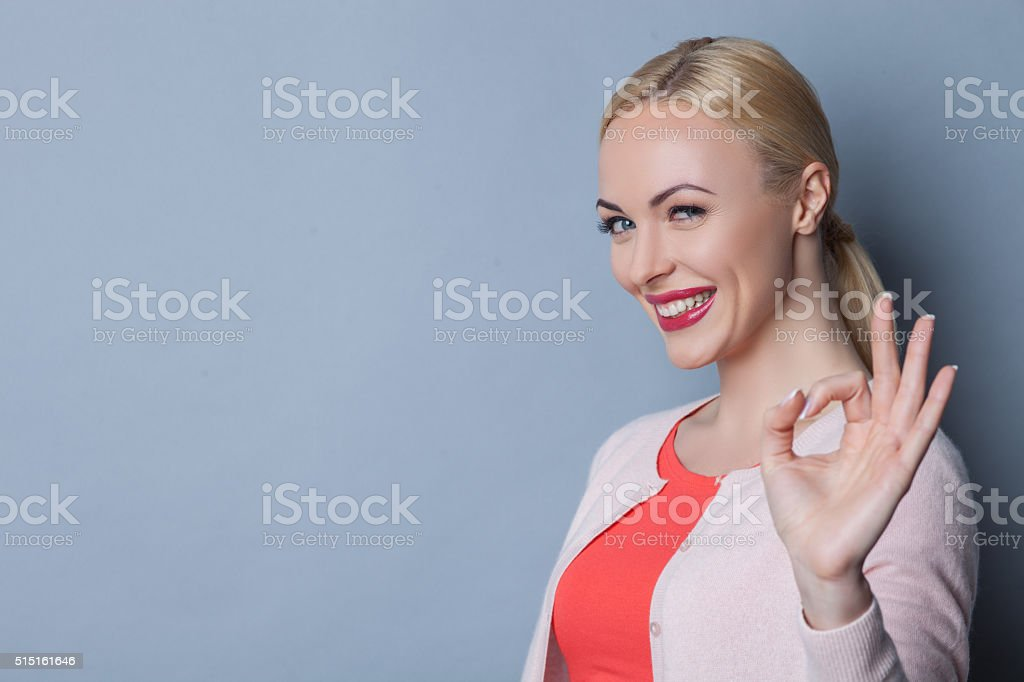 Cheerful young woman is gesturing positively stock photo
