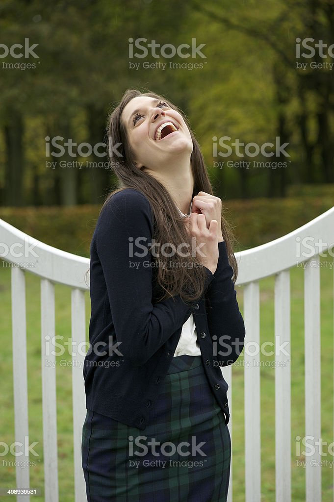 Cheerful young woman laughing outdoors in the park royalty-free stock photo