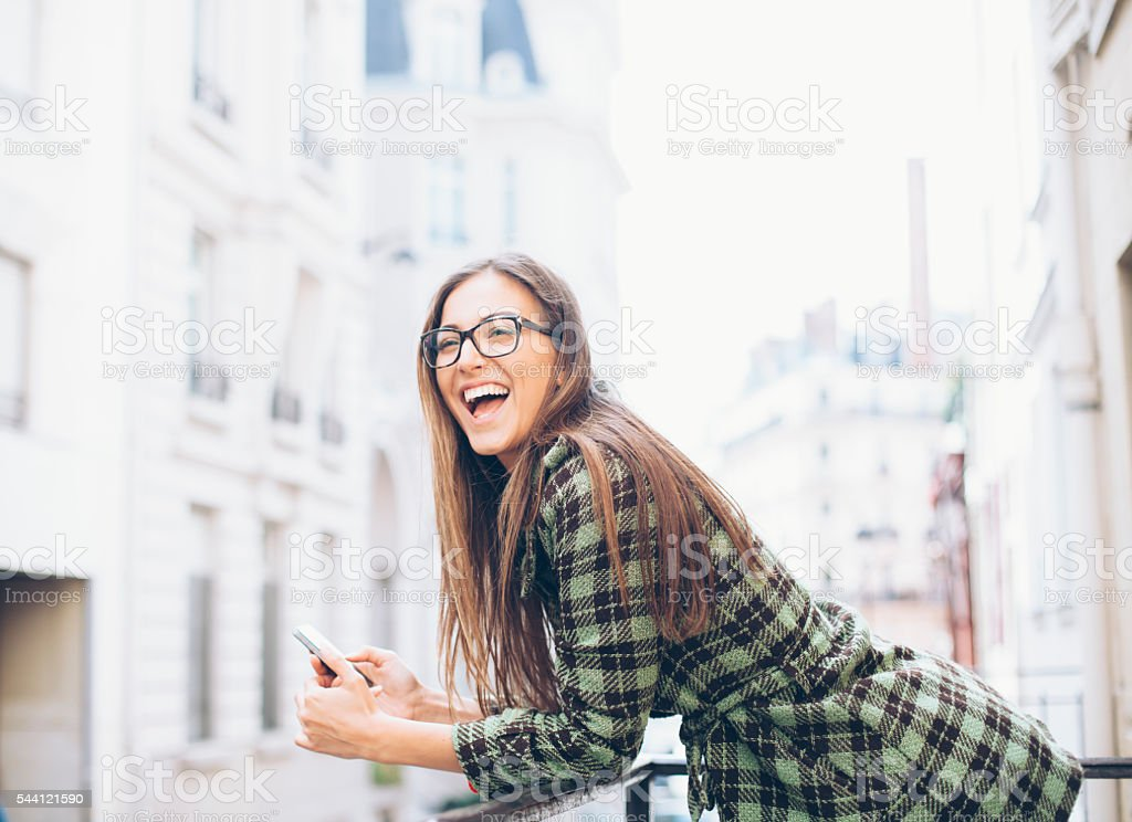 Cheerful young woman leaning on railing and holding phone stock photo