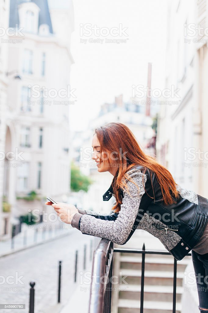 Cheerful young woman leaning on railing and typing stock photo