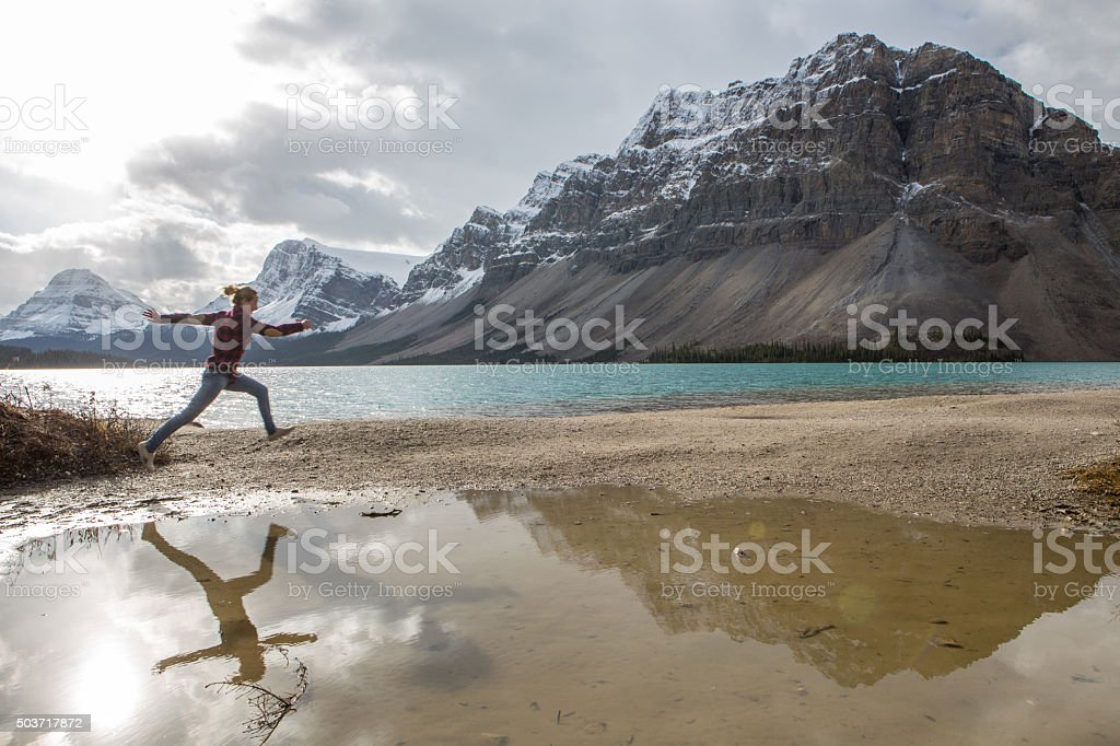 Cheerful young woman leaping mid-air by the lake stock photo