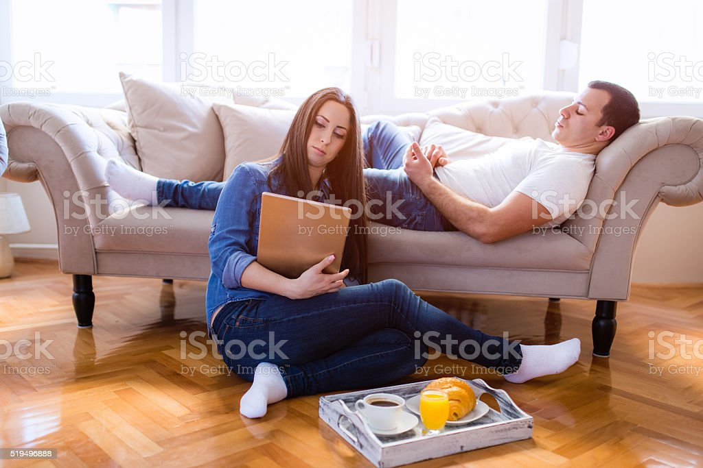 Cheerful young woman listening music in headphones in loft apartment stock photo