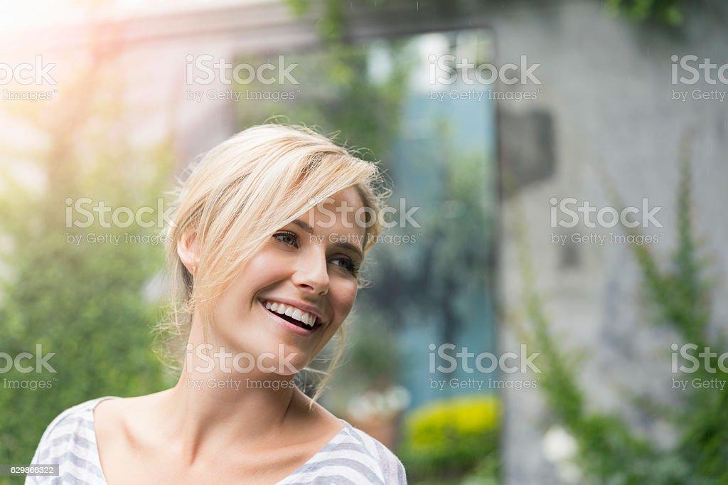 Cheerful young woman looking away at yard stock photo
