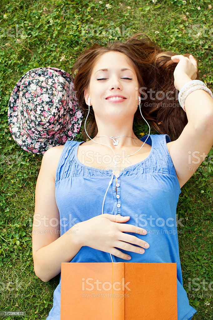 Cheerful Young Woman Lying on grass with book and ipod. royalty-free stock photo