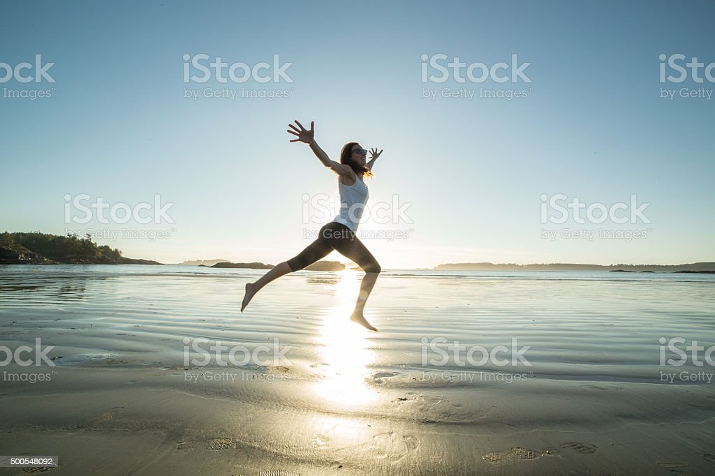 Cheerful young woman on beach jumping for joy and freedom stock photo
