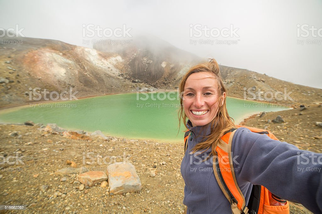 Cheerful young woman photographing herself in nature stock photo