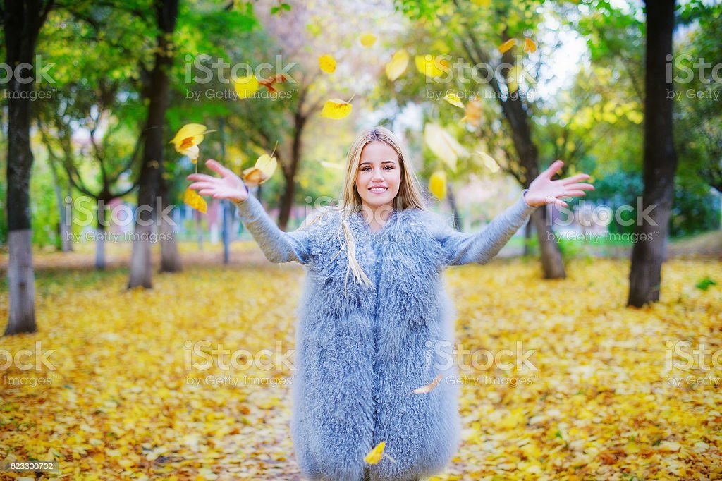 Cheerful young woman playing with autumn leaves stock photo