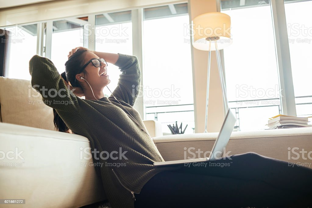 cheerful young woman relaxing after using her laptop stock photo