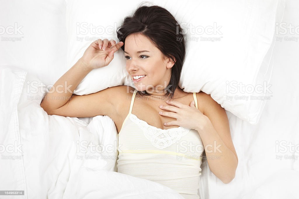 Cheerful Young Woman Relaxing in Bed royalty-free stock photo