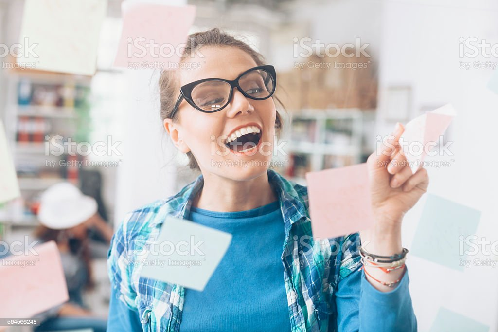 Cheerful young woman removing sticky notes from glass wall stock photo