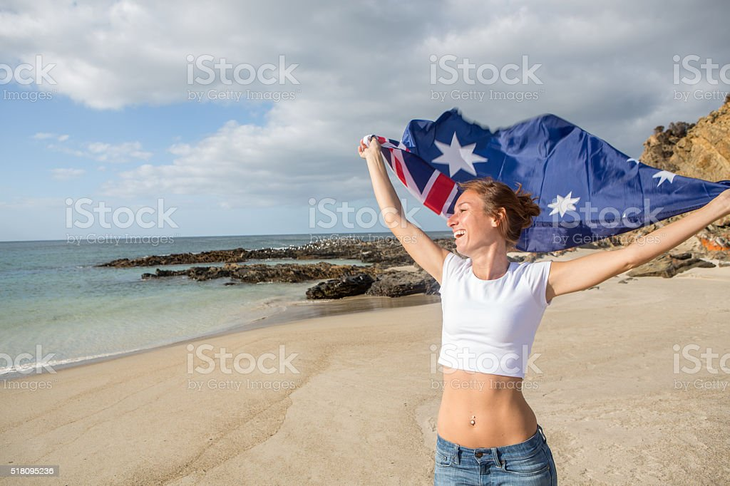 Cheerful young woman runs on beach holding Australian's flag stock photo