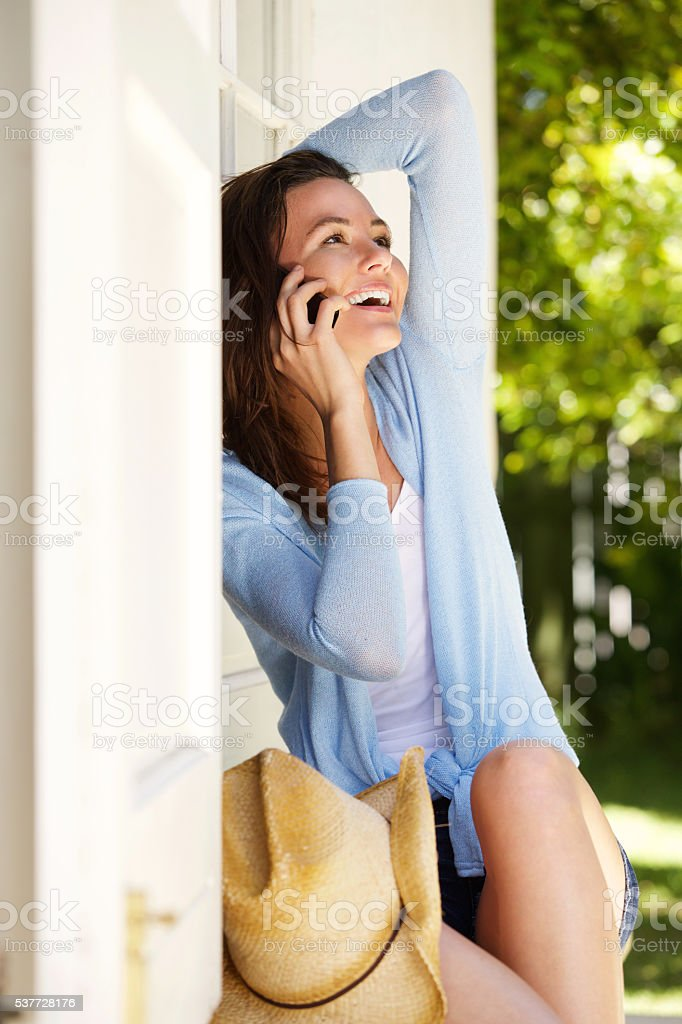 Cheerful young woman sitting outdoors talking a cell phone stock photo