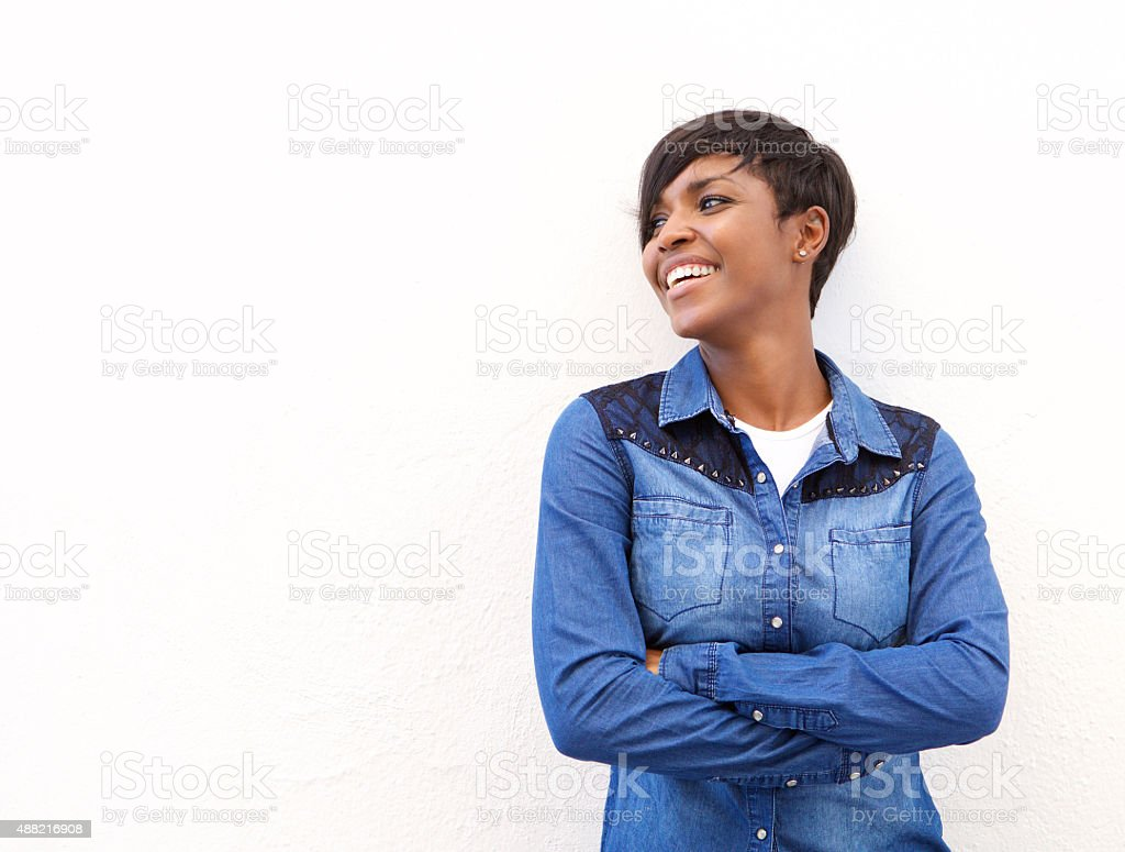 Cheerful young woman standing with arms crossed stock photo