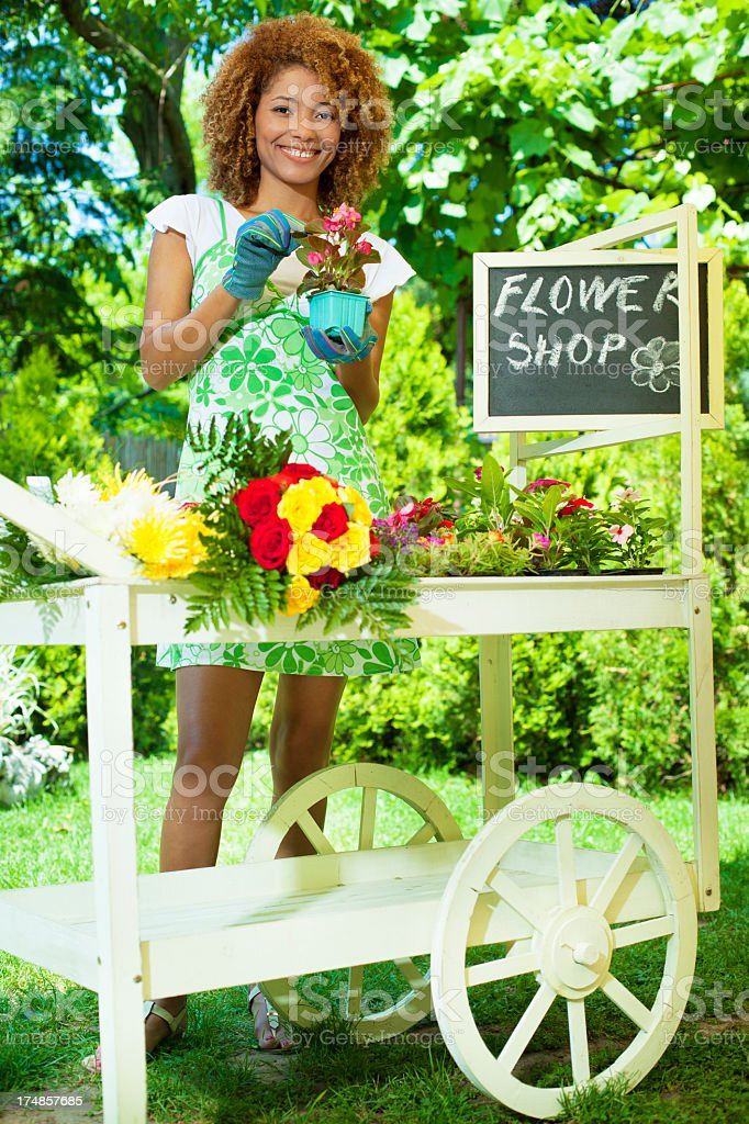 Cheerful Young Woman Standing working with flowers outdoors. royalty-free stock photo