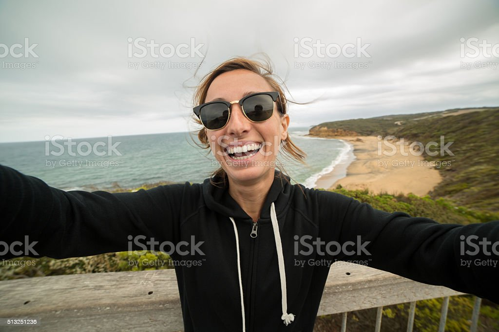 Cheerful young woman takes a selfie portrait on Bells Beach stock photo