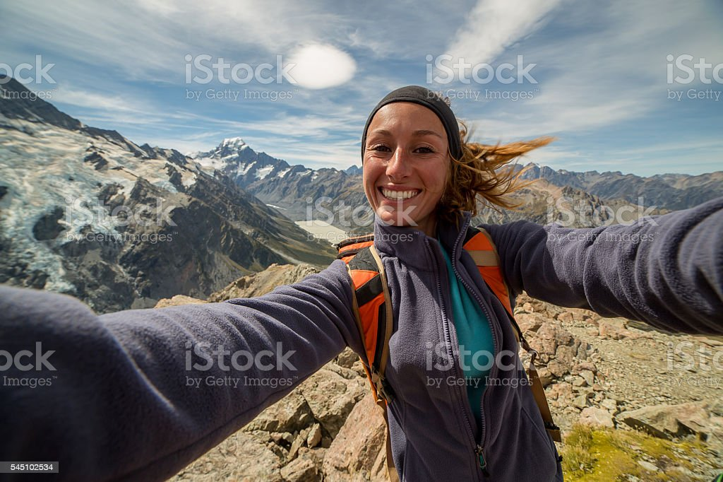 Cheerful young woman takes self portrait on mountain top stock photo