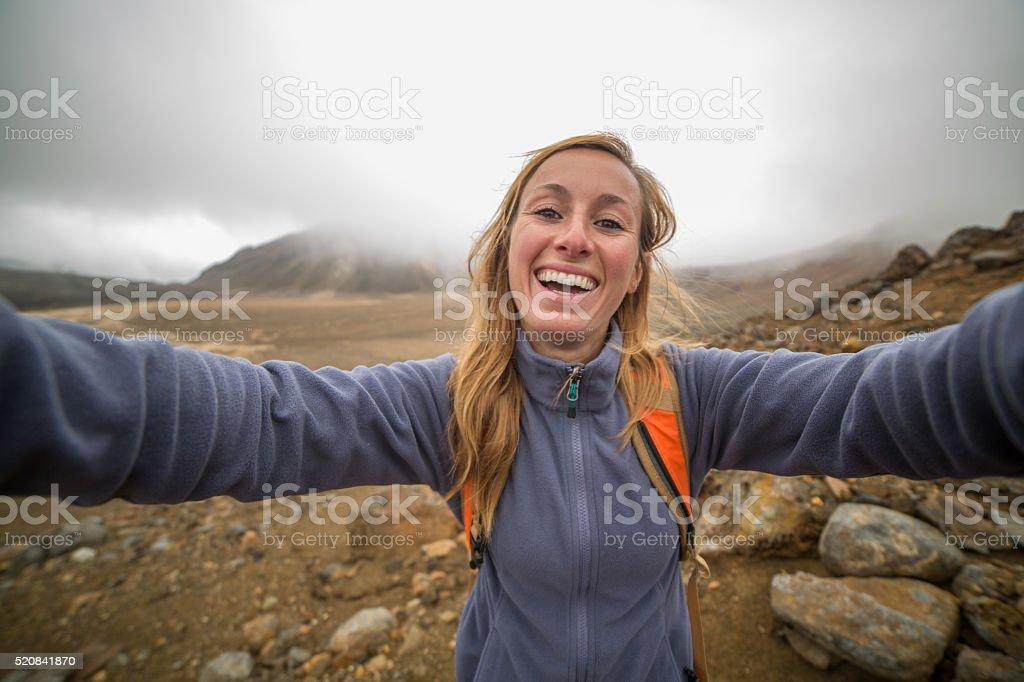 Cheerful young woman takes selfie portrait on Tongariro Alpine Crossing stock photo