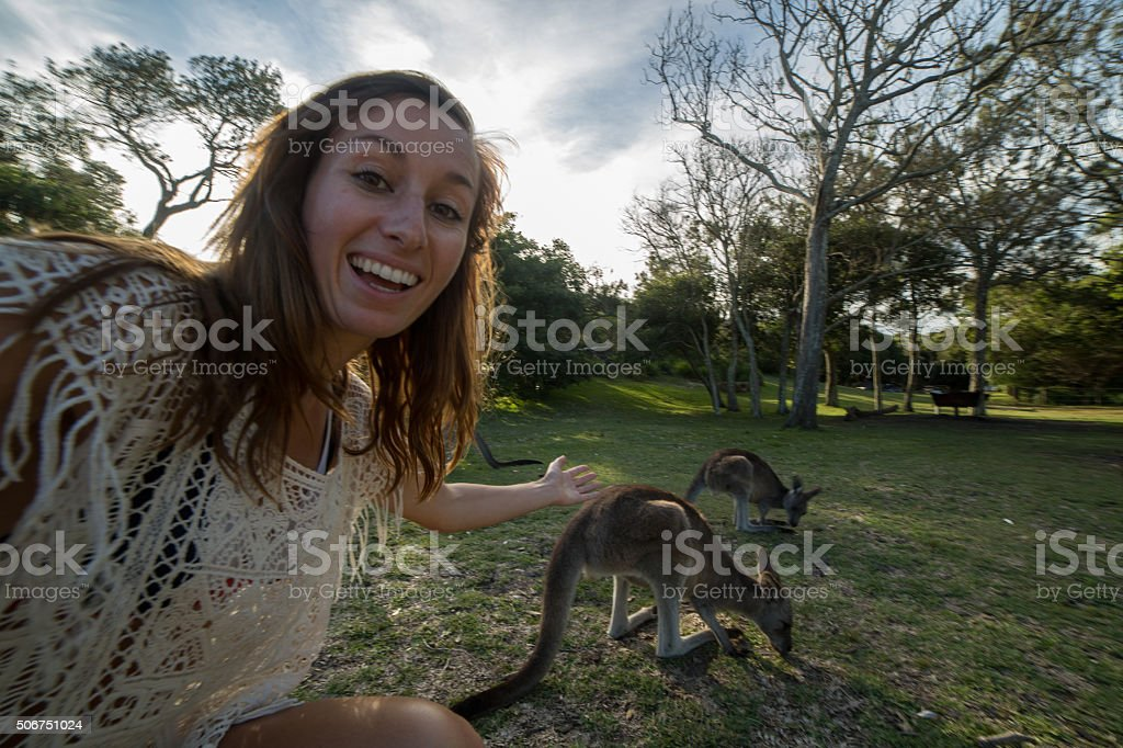 Cheerful young woman takes selfie portrait with kangaroos on background stock photo