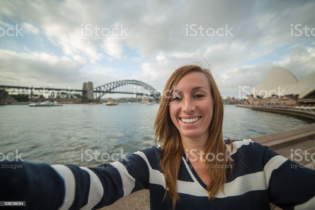 Cheerful young woman takes selfie portrait with Sydney harbor stock photo