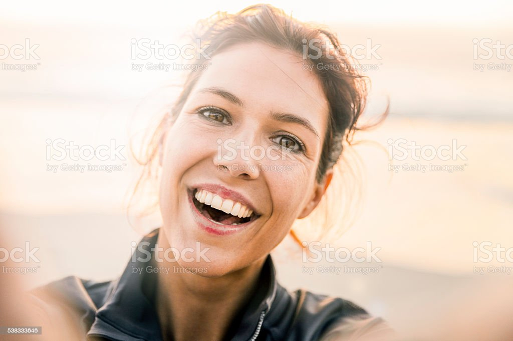 Cheerful young woman taking selfie at beach stock photo