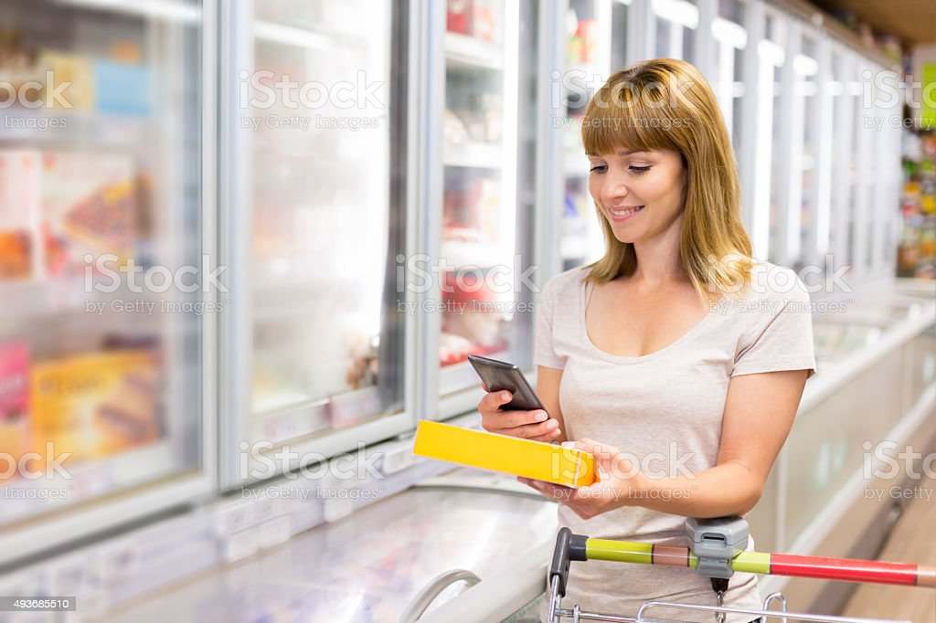 Cheerful young woman texting on mobile phone in supermarket. stock photo