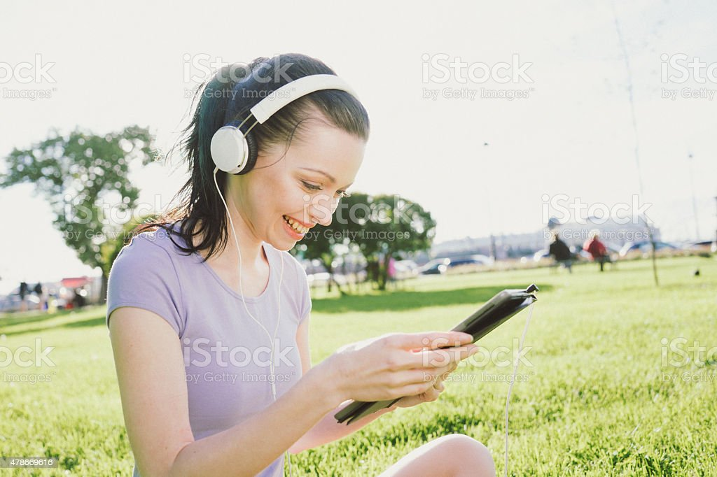 Cheerful Young Woman Using Digital Tablet At The Park stock photo