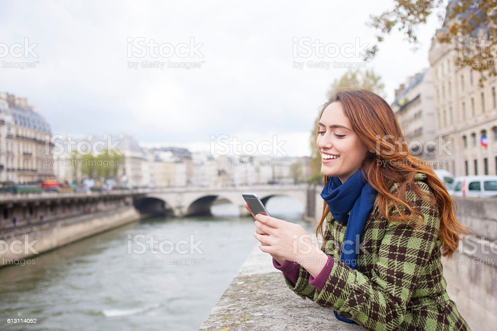 Cheerful young woman using smart phone on a bridge stock photo