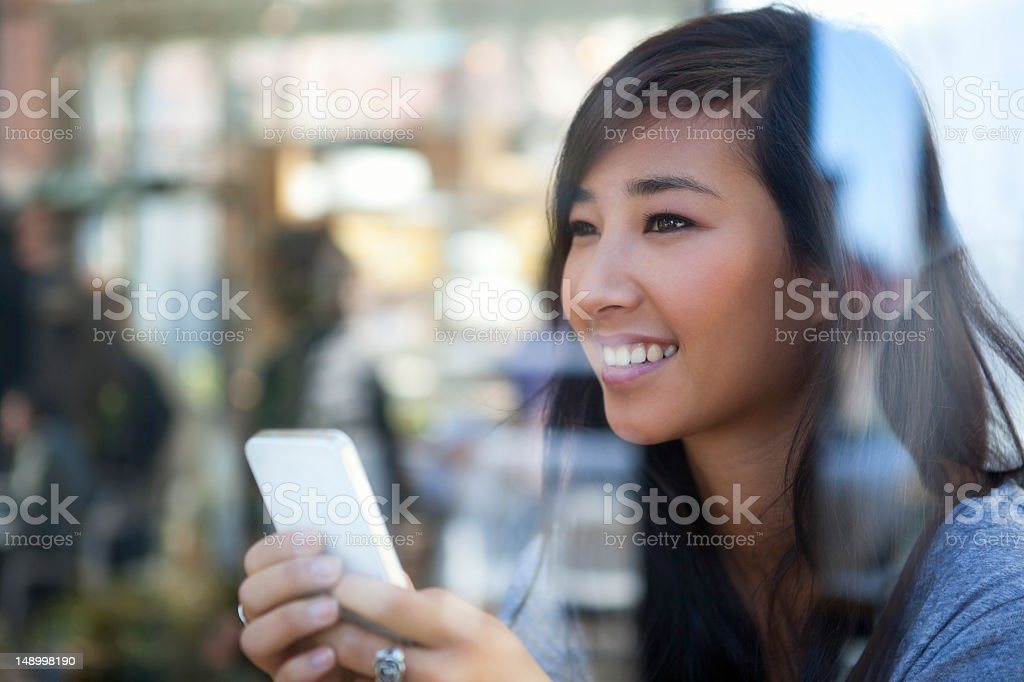 Cheerful young woman using smartphone in coffee shop royalty-free stock photo