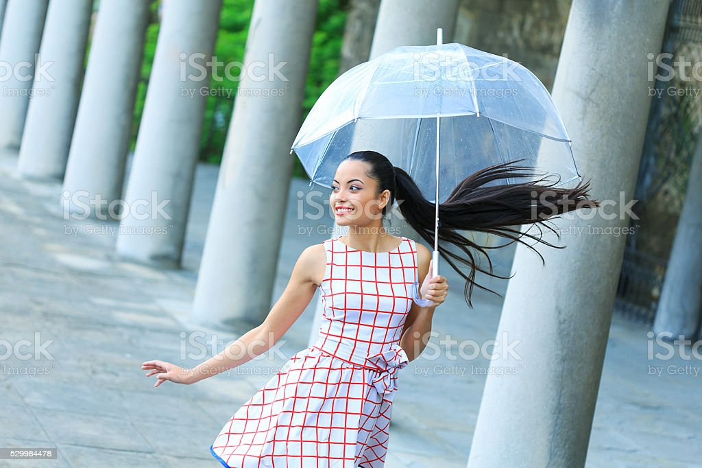 Cheerful young woman walking under the rain stock photo