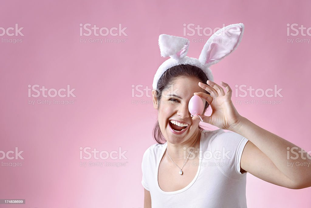 Cheerful young woman wearing bunny ears holding easter egg royalty-free stock photo